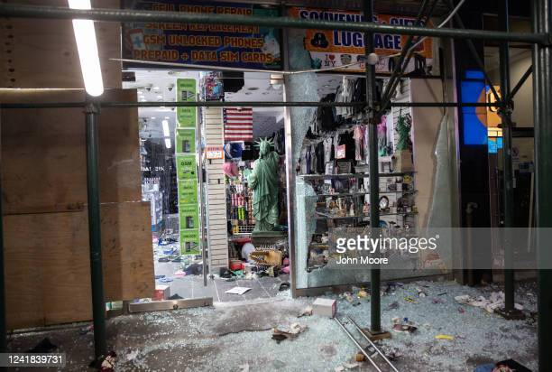 Shattered glass lies in front of a looted souvenir and electronics shop near Times Square after a night of protests and vandalism over the death of...