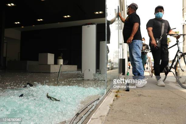 Shattered glass sits in a storefront on Melrose Avenue as passers by access the damage on Sunday May 31 2020