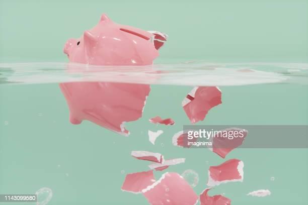 水の中で粉々になった貯金箱 - 経済破綻 ストックフォトと画像