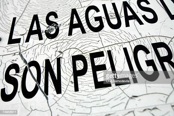 A shattered sign warns people about the dangers of swiming across the Rio Grande near a bridge popular with people illegally crossing the USMexico...