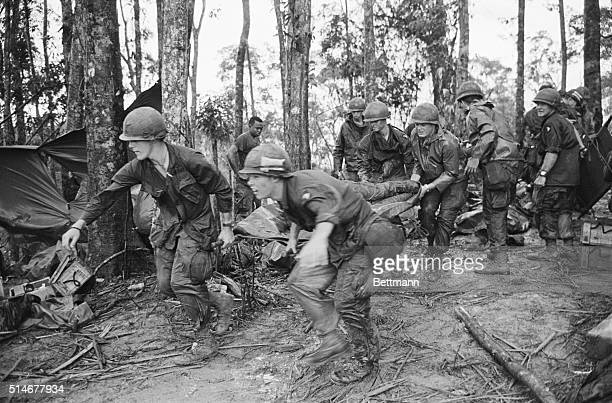 5/18/1969A Shau Valley South Vietnam A quartet of US 101st Air Division troopers keep low as they rush a stretcherborne wounded comrade to a medical...