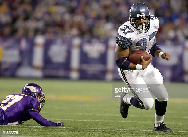 Shaun Alexander of the Seattle Seahawks runs past Brian Russell of the Minnesota Vikings on December 12 2004 at the Hubert H Humphrey Metrodome in...