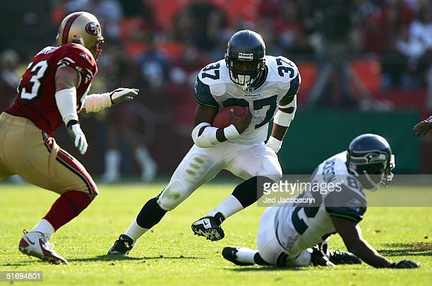 Shaun Alexander of the Seattle Seahawks runs with the ball against Jeff Ulbrich of the San Francisco 49ers at Monster Park on November 7, 2004 in San...