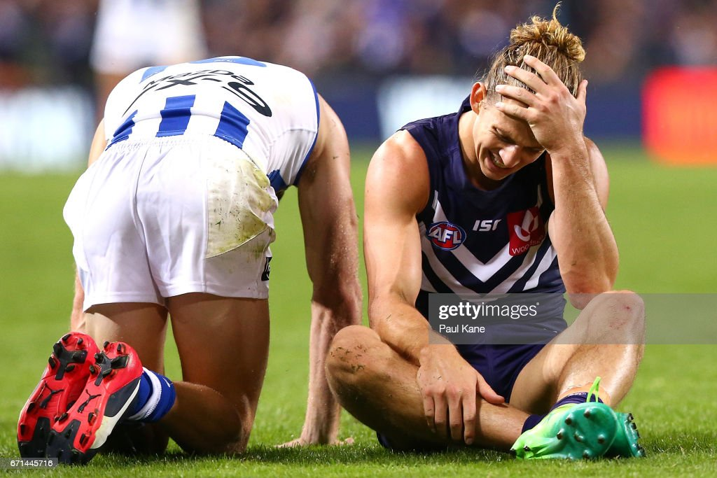 Shaun Atley of the Kangaroos reacts after being defeated while Nathan Fyfe of the Dockers reacts after winning the round five AFL match between the Fremantle Dockers and the North Melbourne Kangaroos at Domain Stadium on April 22, 2017 in Perth, Australia.
