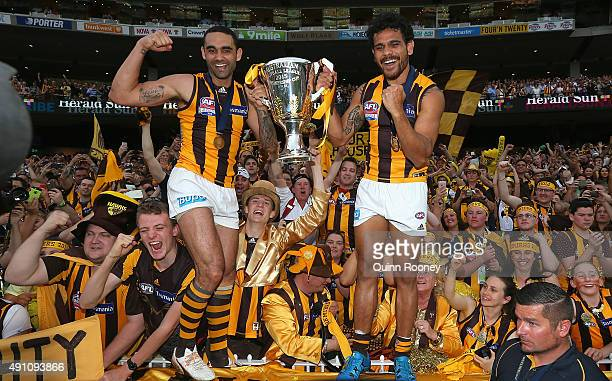 Shaun Burgoyne and Cyril Rioli of the Hawks celebrates with the trophy after winning the 2015 AFL Grand Final match between the Hawthorn Hawks and...