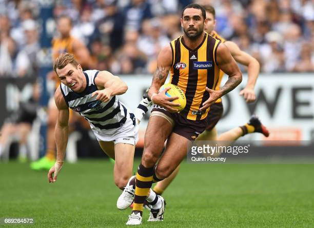 Shaun Burgoyne of the Hawks avoids a tackle by Jackson Thurlow of the Cats during the round four AFL match between the Hawthorn Hawks and the Geelong...