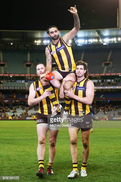 Shaun Burgoyne of the Hawks is carried off by Jarryd Roughead and Ben Stratton for his 350th match during the round 13 AFL match between the Hawthorn...