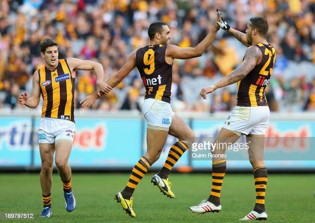 Shaun Burgoyne of the Hawks is congratulated by Lance Franklin and Luke Breust after kicking a goal during the round ten AFL match between the...