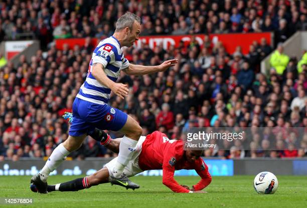 Shaun Derry of Queens Park Rangers brings down Ashley Young of Manchester United to concede a penalty during the Barclays Premier League match...