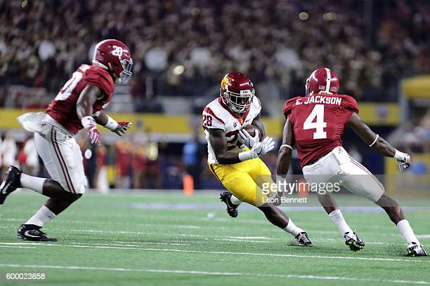 Shaun Dion Hamilton and Eddie Jackson of the Alabama Crimson Tide tackle Aca'Cedric Ware of the USC Trojans in the second half during the AdvoCare...