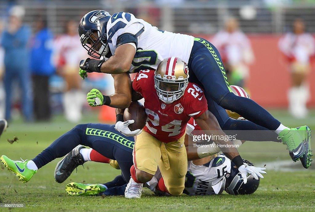 Shaun Draughn #24 of the San Francisco 49ers gets tackled by K.J. Wright #50 and Cassius Marsh #91 of the Seattle Seahawks during the fourth quarter of their NFL football game at Levi's Stadium on January 1, 2017 in Santa Clara, California.