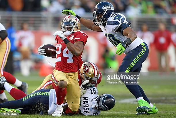 Shaun Draughn of the San Francisco 49ers gets tackled by KJ Wright and Cassius Marsh of the Seattle Seahawks during the fourth quarter of their NFL...