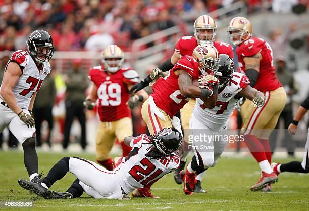 Shaun Draughn of the San Francisco 49ers is tackled by Desmond Trufant and Ra'Shede Hageman Atlanta Falcons at Levi's Stadium on November 8 2015 in...