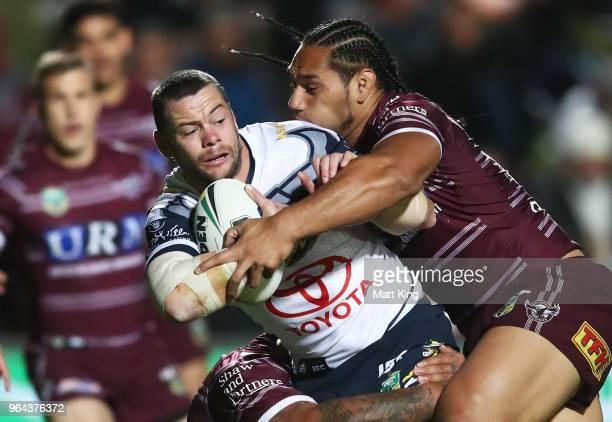 Shaun Fensom of the Cowboys is tackled by Martin Taupau of the Sea Eagles during the round 13 NRL match between the Manly Sea Eagles and the North...