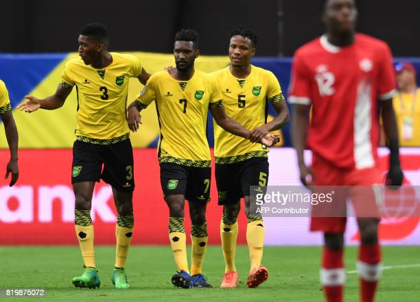 Shaun Francis of Jamaica is escorted by teammates after his goal against Canada in the first half of their CONCACAF Gold Cup quarterfinal match July...