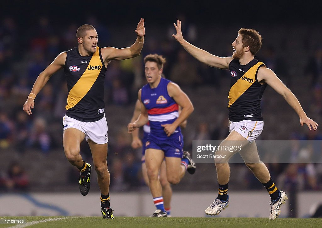Shaun Grigg (L) of the Tigers celebrates after kicking a goal during the round 13 AFL match between the Western Bulldogs and the Richmond Tigers at Etihad Stadium on June 22, 2013 in Melbourne, Australia.