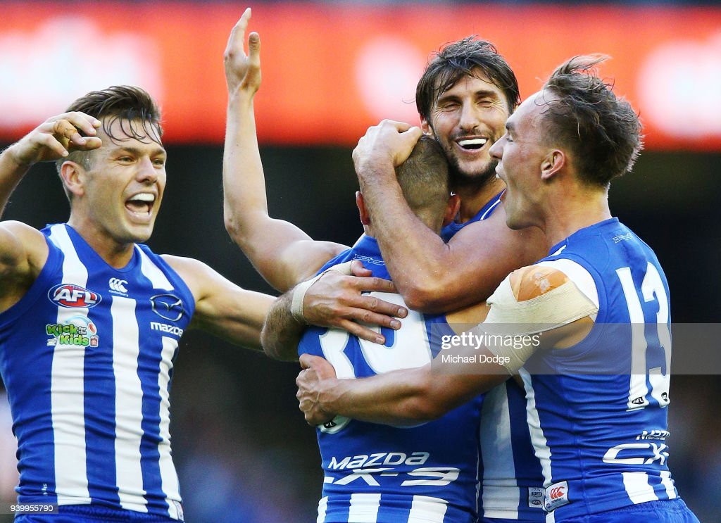 Shaun Higgins (L) Jarrad Waite and Ryan Clarke of the Kangaroos all hug Billy Hartung of the Kangaroos as he celebrate a goal during the round two AFL match between the North Melbourne Kangaroos and the St Kilda Saints at Etihad Stadium on March 30, 2018 in Melbourne, Australia.