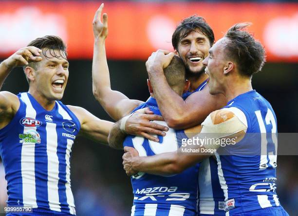 Shaun Higgins Jarrad Waite and Ryan Clarke of the Kangaroos all hug Billy Hartung of the Kangaroos as he celebrate a goal during the round two AFL...