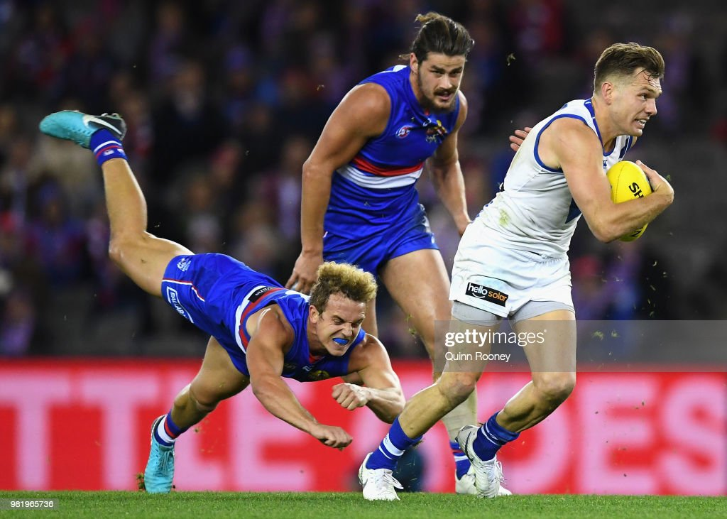 Shaun Higgins of the Kangaroos breaks free of a tackle by Mitch Wallis of the Bulldogs during the round 14 AFL match between the Western Bulldogs and the North Melbourne Kangaroos at Etihad Stadium on June 23, 2018 in Melbourne, Australia.