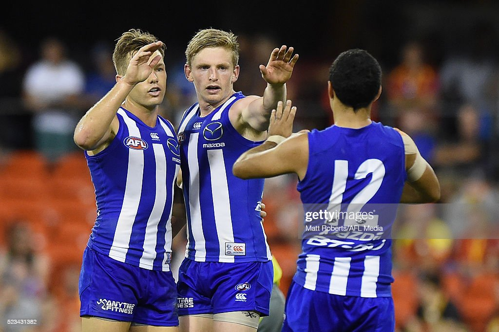 Shaun Higgins of the Kangaroos celebrates kicking a goal with team mates during the round five AFL match between the Gold Coast Suns and the North Melbourne Kangaroos at Metricon Stadium on April 23, 2016 in Gold Coast, Australia.