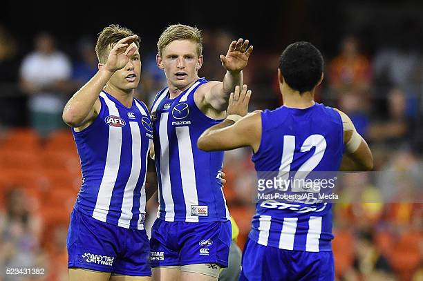 Shaun Higgins of the Kangaroos celebrates kicking a goal with team mates during the round five AFL match between the Gold Coast Suns and the North...