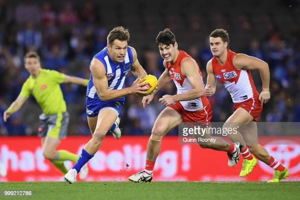 Shaun Higgins of the Kangaroos clears the ball out of the centre during the round 17 AFL match between the North Melbourne Kangaroos and the Sydney...