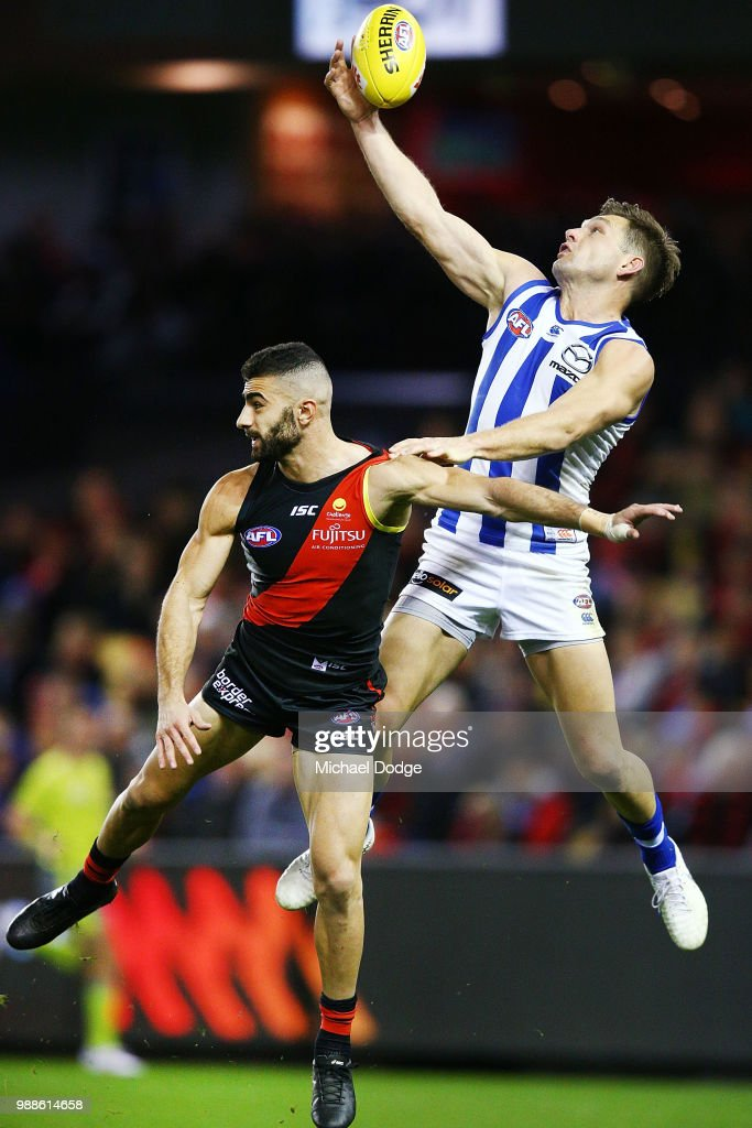 Shaun Higgins of the Kangaroos competes for the ball against Adam Saad of the Bombers during the round 15 AFL match between the Essendon Bombers and the North Melbourne Kangaroos at Etihad Stadium on July 1, 2018 in Melbourne, Australia.