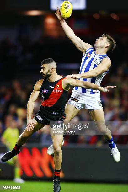 Shaun Higgins of the Kangaroos competes for the ball against Adam Saad of the Bombers during the round 15 AFL match between the Essendon Bombers and...