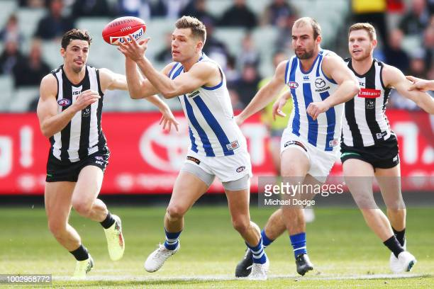 Shaun Higgins of the Kangaroos gathers the ball from Scott Pendlebury of the Magpies during the round 18 AFL match between the Collingwood Magpies...