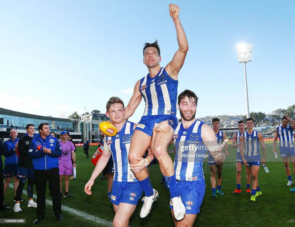 Shaun Higgins of the Kangaroos gets carried off by Jack Ziebell (L) and Luke McDonald after winning his 200th match during the round 19 AFL match between the North Melbourne Kangaroos and the West Coast Eagles at Blundstone Arena on July 29, 2018 in Hobart, Australia.