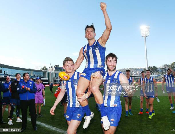 Shaun Higgins of the Kangaroos gets carried off by Jack Ziebell and Luke McDonald after winning his 200th match during the round 19 AFL match between...