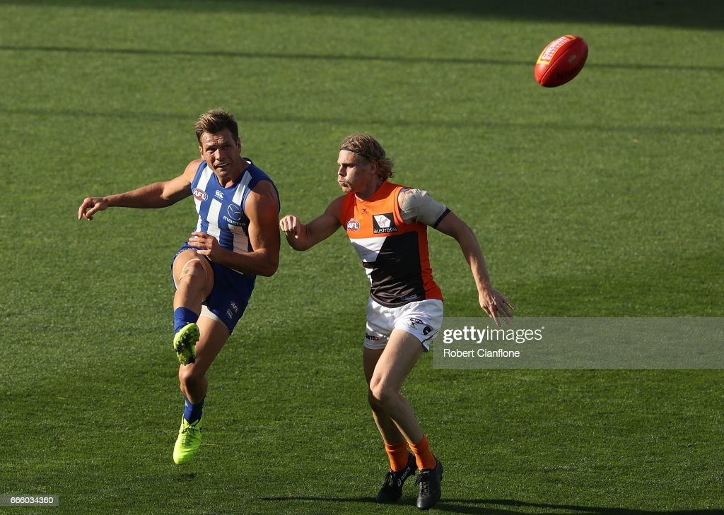 Shaun Higgins of the Kangaroos gets his kick away from Adam Kennedy of the Giants during the round three AFL match between the North Melbourne Kangaroos and the Greater Western Sydney Giants at Blundstone Arena on April 8, 2017 in Hobart, Australia.