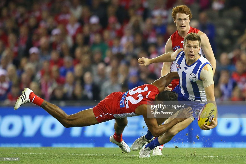 Shaun Higgins of the Kangaroos handballs whilst being tackled by Lewis Jetta of the Swans during the round 11 AFL match between the North Melbourne Kangaroos and the Sydney Swans at Etihad Stadium on June 13, 2015 in Melbourne, Australia.