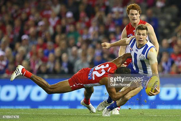 Shaun Higgins of the Kangaroos handballs whilst being tackled by Lewis Jetta of the Swans during the round 11 AFL match between the North Melbourne...
