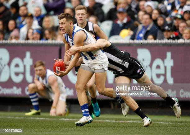 Shaun Higgins of the Kangaroos is tackled by Brayden Maynard of the Magpies during the 2018 AFL round 18 match between the Collingwood Magpies and...