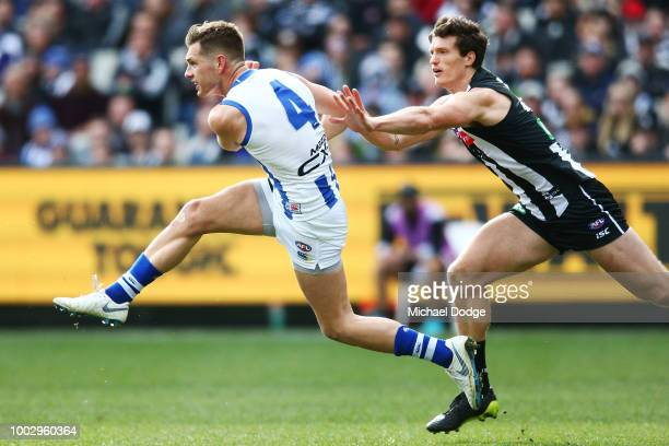 Shaun Higgins of the Kangaroos kicks the ball from Brody Mihocek of the Magpies during the round 18 AFL match between the Collingwood Magpies and the...