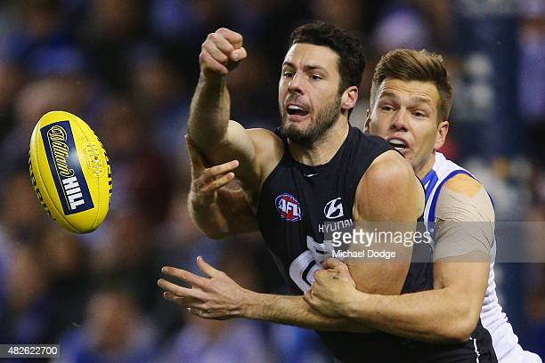 Shaun Higgins of the Kangaroos tackles Simon White of the Blues during the round 18 AFL match between the Carlton Blues and the North Melbourne...