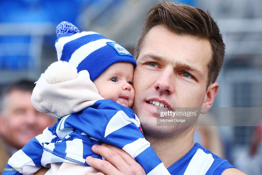 Shaun Higgins of the Kangaroos walks out with his baby for his 200th match during the round 19 AFL match between the North Melbourne Kangaroos and the West Coast Eagles at Blundstone Arena on July 29, 2018 in Hobart, Australia.