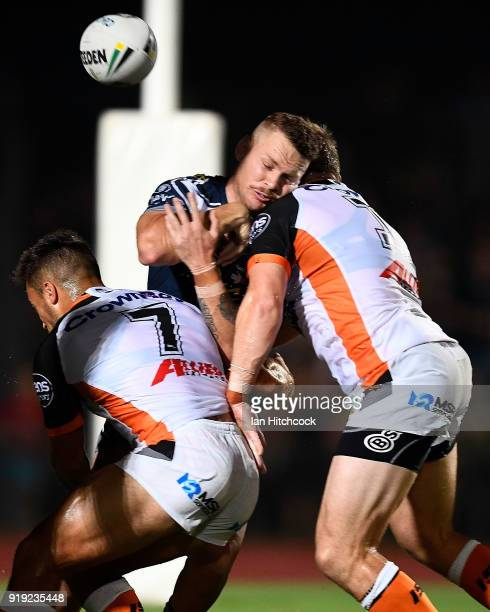Shaun Hudson of the Cowboys has the ball knocked out of his arms after being tackled by Luke Brooks and Chris Lawrence of the Tigers during the NRL...