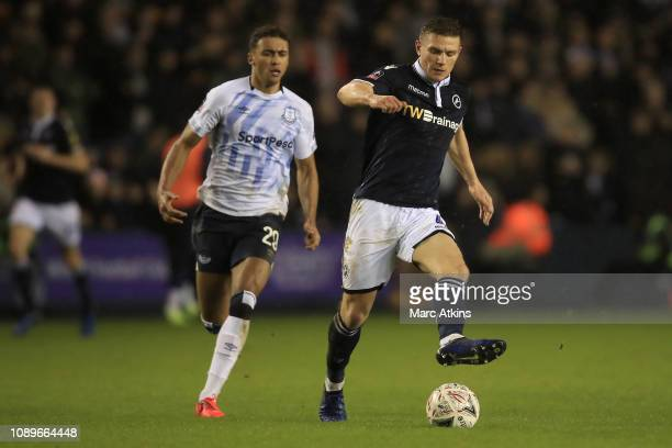 Shaun Hutchinson of Millwall runs with the ball under pressure from Dominic CalvertLewin of Everton during the FA Cup Fourth Round match between...