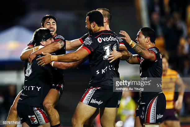 Shaun Johnson and the Warriors teammates rush in to celebrate Jacob Lillyman's try during the round 13 NRL match between the New Zealand Warriors and...