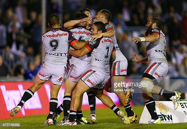 Shaun Johnson of the Warriors celebrates his winning try with team mates during the round nine NRL match between the Sharks and the Warriors at...