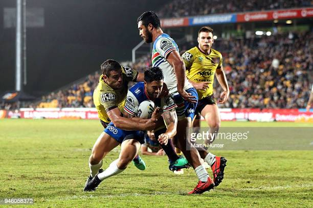 Shaun Johnson of the Warriors drives over to score a try in the tackle of Andrew McCullough of the Broncos during the round six NRL match between the...