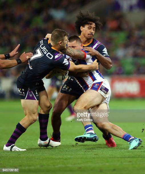 Shaun KennyDowall of the Knights is tackled by Ryley Jacks and Felise Kaufusi of the Storm during the round six NRL match between the Melbourne Storm...