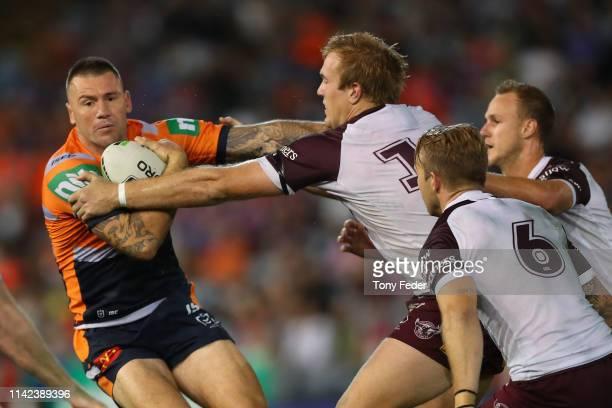 Shaun Kenny-Dowall of the Newcastle Knights is tackled by the Manly defence during the round five NRL match between the Newcastle Knights and the...