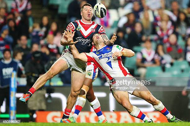 Shaun KennyDowall of the Roosters competes for a high ball with James McManus of the Knights to score a try during the round 14 NRL match between the...