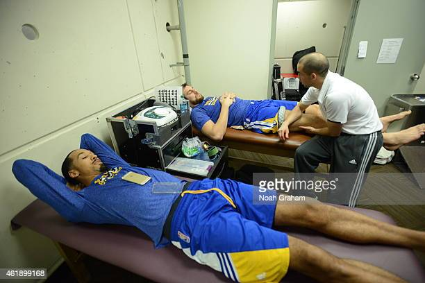 Shaun Livingston and Andrew Bogut of the Golden State Warriors get taped up by JoHan Wang before the game against the Utah Jazz on January 13 2015 in...