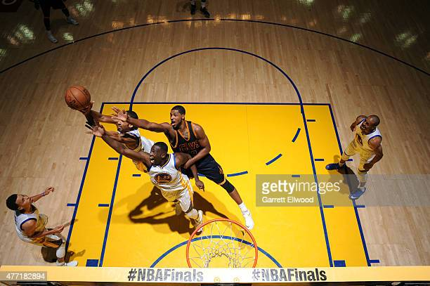 Shaun Livingston and Draymond Green of the Golden State Warriors jump for a rebound against Tristan Thompson of the Cleveland Cavaliers in Game Five...