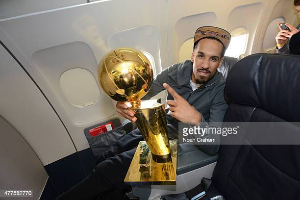 Shaun Livingston of the Golden State Warriors holds the NBA trophy on the plane as the team travels home from Cleveland after winning the 2015 NBA...