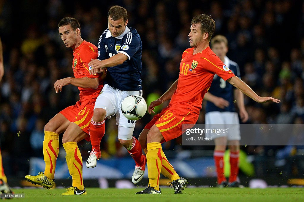 Shaun Maloney of Scotland goes past Vanche Shikov and Muhamed Demiri of Macedonia during the FIFA World Cup Qualifier Between Scotland and Macedonia at Hampden Park on September 11, 2012 in Glasgow, Scotland.